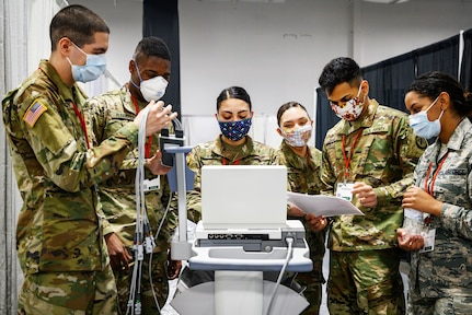 A group of guardsmen test medical equipment at a field medical station.