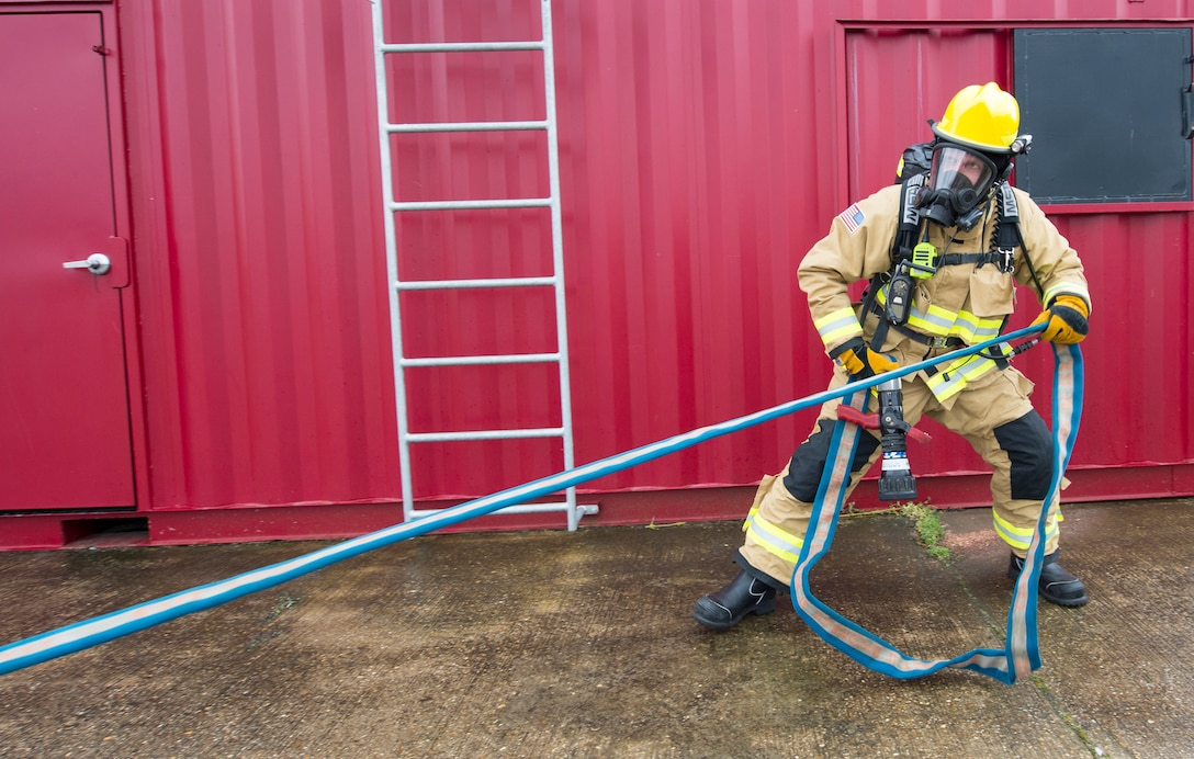 A firefighter with the 423rd Civil Engineer Squadron secures a firehose during confined spaces training at RAF Alconbury, England on March 30, 2020. This type of training helps the firefighters maintain readiness and stay proficient in their craft. (U.S. Air Force photo by Master Sgt. Brian Kimball)