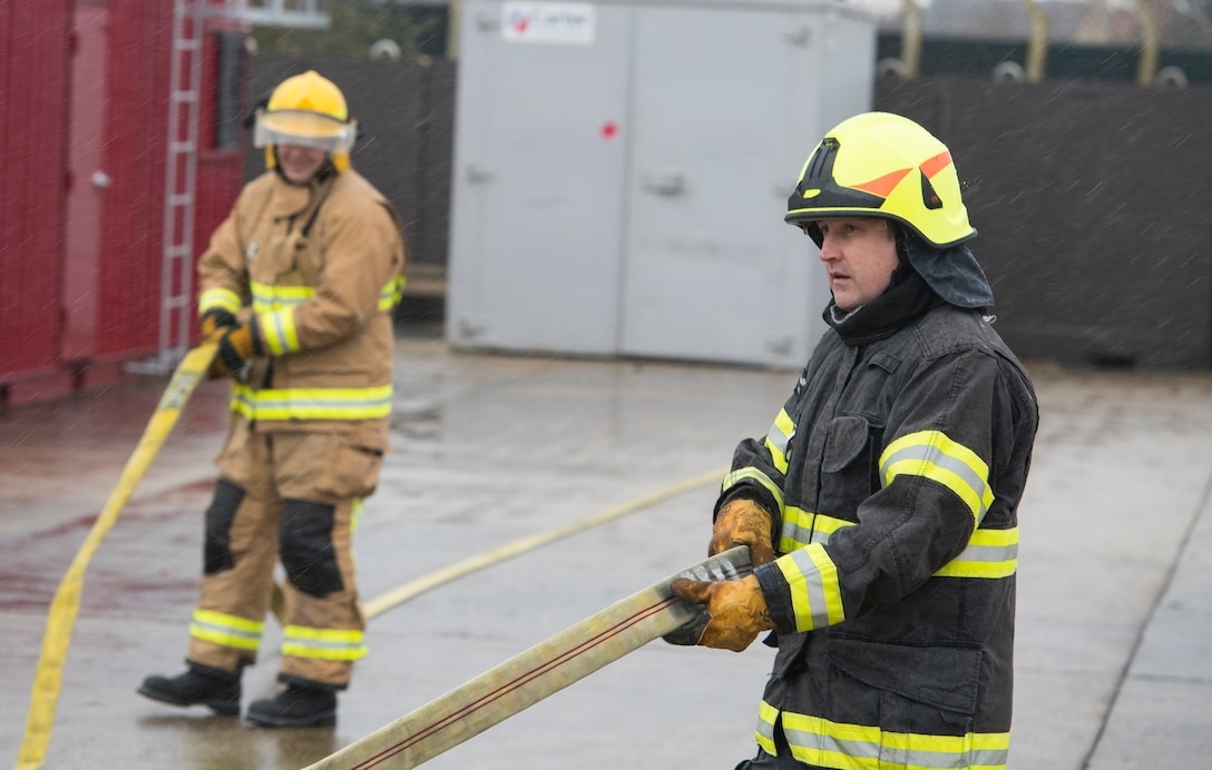 Firefighters with the 423rd Civil Engineer Squadron roll up a firehose during confined spaces training at RAF Alconbury, England on March 30, 2020. This type of training helps the firefighters maintain readiness and stay proficient in their craft. (U.S. Air Force photo by Master Sgt. Brian Kimball)