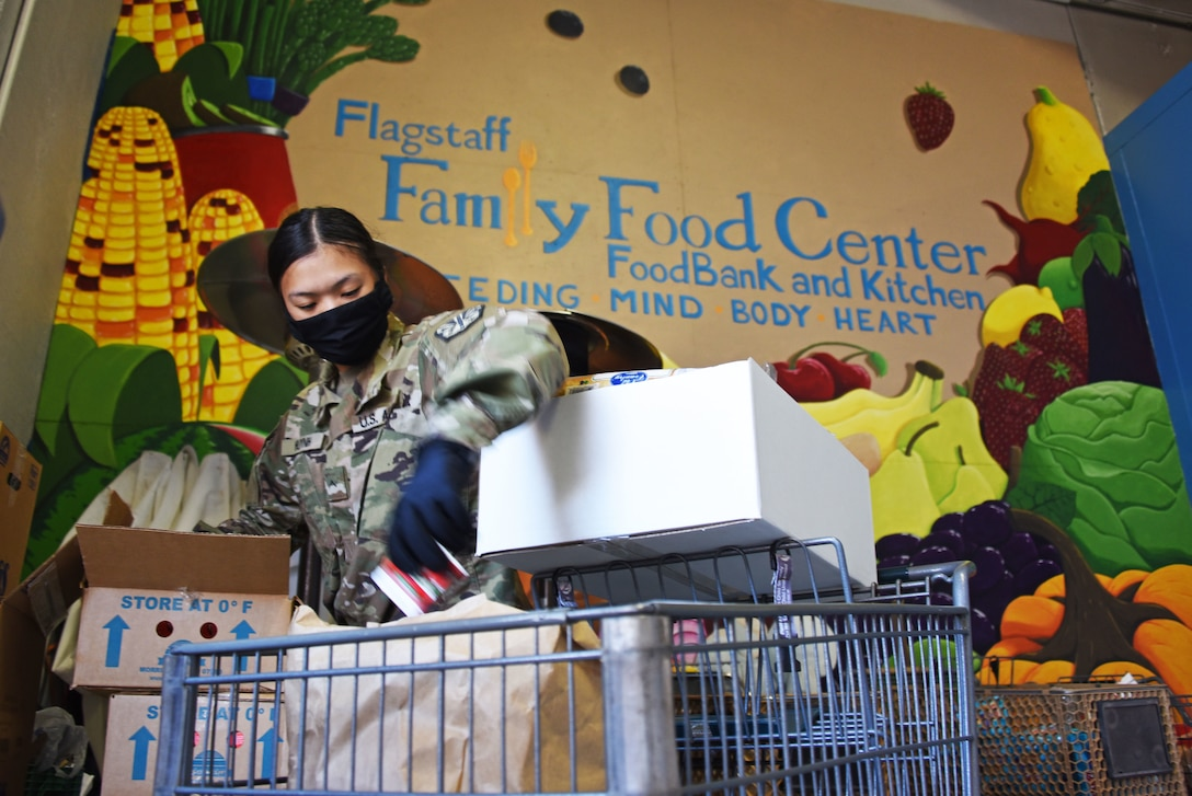 Guardsman prepares boxes of fresh produce and groceries for distribution.