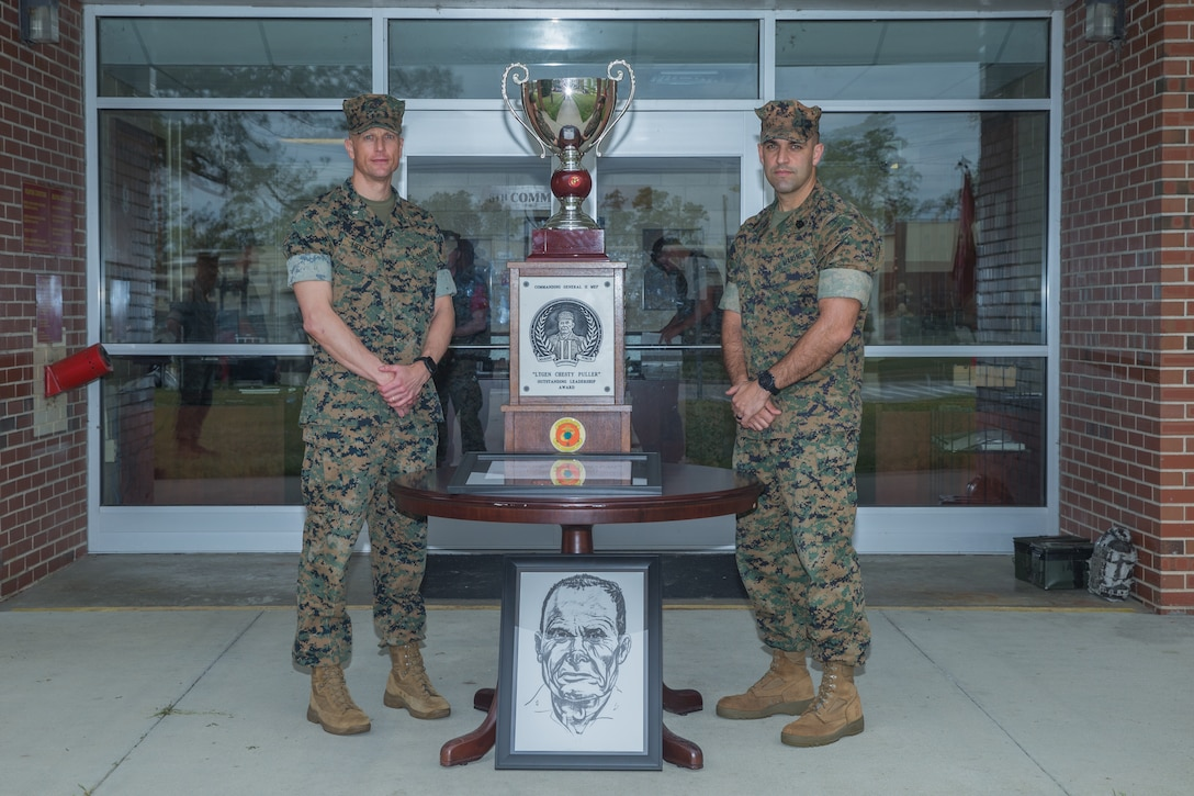 """Lt. Col. Thomas Heller (left), the commanding officer of 8th Communication Battalion, II MEF Information Group, and Sgt. Maj. Joyuanki Victore, sergeant major of 8th Comm., pose for a photo beside the """"Lieutenant General Chesty Puller Outstanding Leadership Award"""" (Large Unit Category) trophy and citation at Camp Lejeune, N.C.,"""