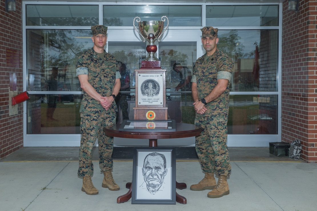 "Lt. Col. Thomas Heller (left), the Commanding Officer of 8th Communication Battalion, II MEF Information Group, and Sgt. Maj. Joyuanki Victore, sergeant major of 8th Comm., pose for a photo beside the ""Lieutenant General Chesty Puller Outstanding Leadership Award"" (Large Unit Category) trophy and citation at Camp Lejeune, N.C.,"