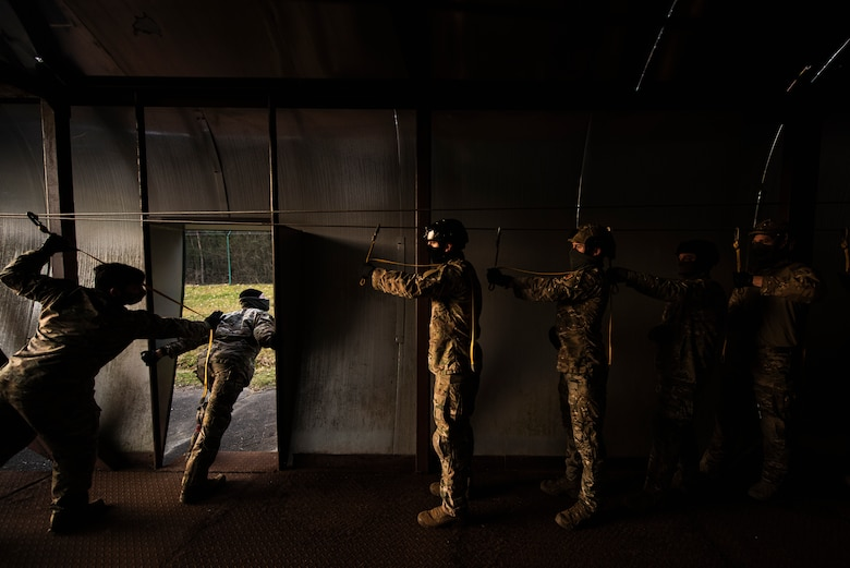 Airmen are standing inside a C-130 training model at sunrise.