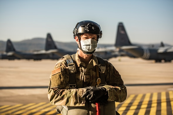 An Airman poses with their parachute on in front of C-130J Super Hercules aircraft.