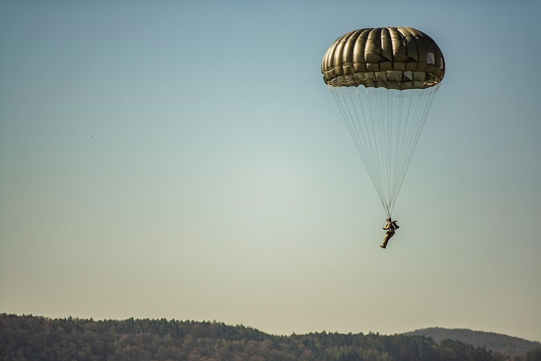 An airborne Airman controls decent of parachuting over the Germany skyline.