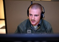 Senior Airman Connor Martin, crew chief, 157th Air Refueling Wing, New Hampshire Air National Guard, works at a makeshift call center at the state fire academy in Concord, April 7, 2020.