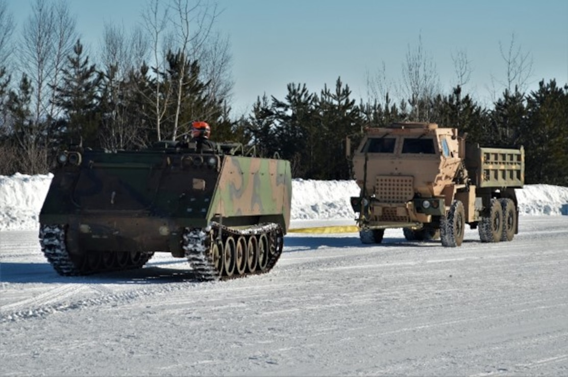 Military vehicles on an icy road.