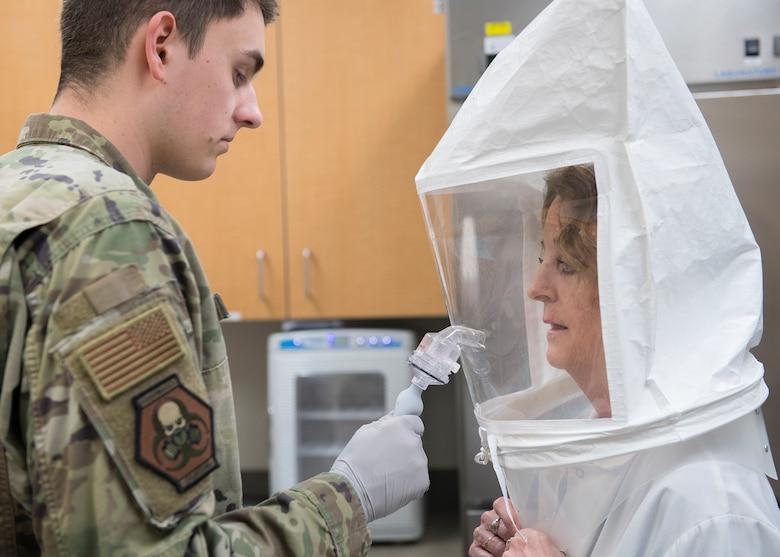 Senior Airman Andrew Hetzler, 56th Bioenvironmental Engineer technician, mists a bitter sensitivity solution in to a qualitative fit test hood worn by Karen St. Aubin, 56th Dental Squadron dental technician, April 1, 2020, at Luke Air Force Base, Ariz.