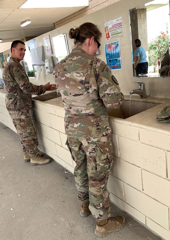 Soldiers assigned to Task Force Spartan Shield wash their hands at the entrance of a dining facility April 8, 2020, in the U.S. Central Command area of operations. To help prevent the spread of COVID-19, the Centers for Disease Control and Prevention recommends washing your hands often with soap and water for at least 20 seconds. The CDC also recommends disinfecting frequently touched surfaces, avoiding close contact with those who are sick, covering coughs and sneezes with a tissue, cloth, or the inside of your elbow and observing social distancing guidance. (U.S. Army National Guard photo by Master Sgt. Thomas Wheeler, Task Force Spartan Public Affairs)