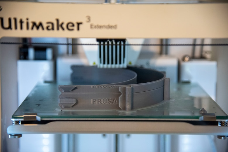 """A 3D printer creates face shield adjustable headbands on April 7, 2020 at Dover Air Force Bace, Delaware. The face shields were printed by the 436th Airlift Wing Innovation Lab """"Bedrock"""" for use by medical and security forces personnel supporting COVID-19 response efforts. (U.S. Air Force photo by Airman 1st Class Jonathan Harding)"""