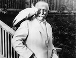 Dr. John H. Kellogg with a cockatoo on his shoulder.