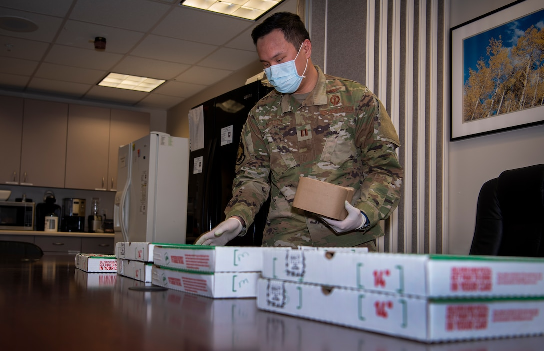 """Capt. Ronald Nguyen, 50th Space Wing Safety Office chief of safety, delivers pizza to the base clinic April 8, 2020, at Schriever Air Force Base, Colorado. In light of COVID-19 precautions, Nguyen made """"contactless"""" deliveries, dropping off the pizzas to an empty space, to multiple units on base where the mission continues. (U.S. Air Force photo by Airman Amanda Lovelace)"""
