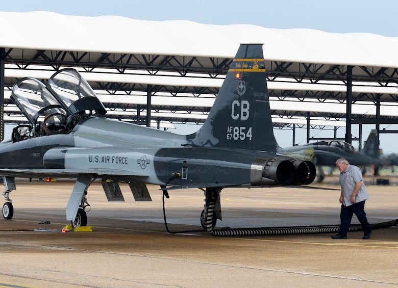 An M1 Support Services maintainer conducts preflight checks on a T-38 Talon, while two 14th Flying Training Wing pilots sit in the cockpit April 8, 2020, at Columbus Air Force Base, Miss. The Air Education and Training Command is the primary user of the T-38 for joint specialized undergraduate pilot training. Pilot training has been deemed essential operations and continues amid the COVID-19 pandemic. (U.S. Air Force photo by Airman 1st Class Davis Donaldson)