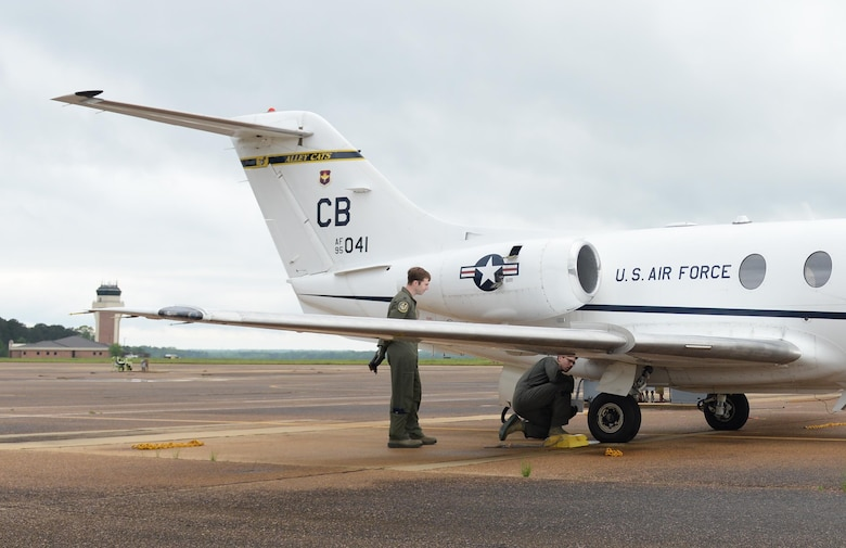Two 14th Flying Training Wing pilots conduct preflight checks on a T-1A Jayhawk April 9, 2020, at Columbus Air Force Base, Miss. The T-1 is a medium-range, twin-engine jet trainer used in the advanced phase of specialized undergraduate pilot training for students selected to fly airlift or tanker aircraft. Pilot training has been deemed essential operations and continues amid the COVID-19 pandemic. (U.S. Air Force photo by Airman 1st Class Davis Donaldson)