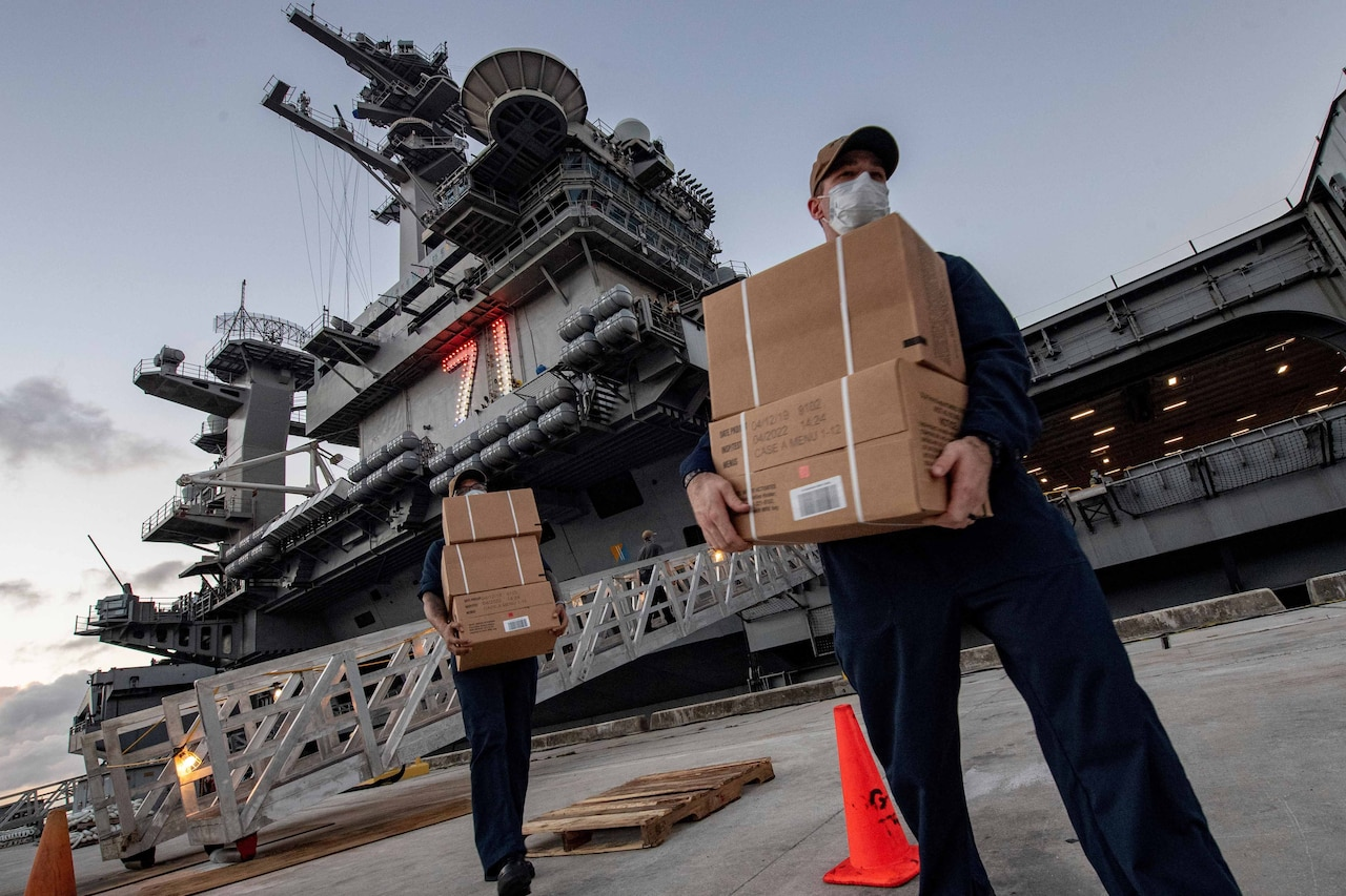 Two military personnel carry cardboard boxes. Both wear masks. In the background is an aircraft carrier.