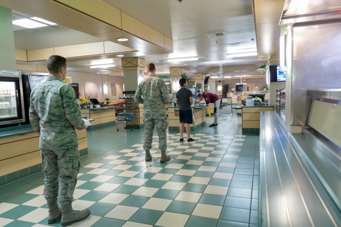 Airmen from Edwards Air Force Base, California, file in line for a meal at the base dining facility maintaining appropriate physical distance, April 7.