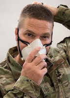 An Airman puts on a mask.