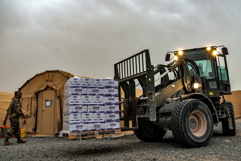 heavy equipment operator transports cases of water