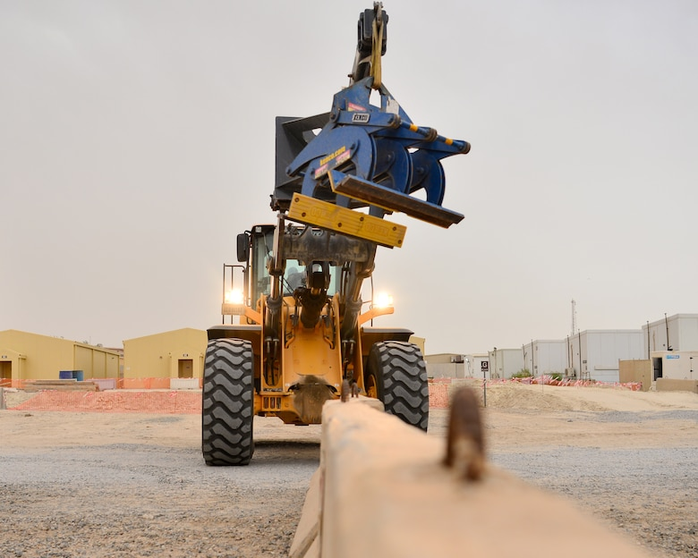 Airman uses heavy equipment to move barriers