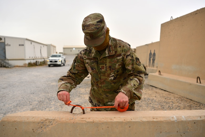 Airman ties reflective tape to barrier