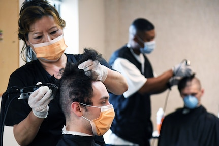 A female barber wearing personal protective equipment gives a new recruit the signature close-cropped haircut.