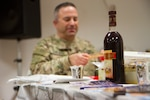 A bottle of wine sits ready as Maj. Andrew Schulman, a rabbi with the 7th Mission Support Command in Kaiserslautern, Germany, breaks matzah during a Jewish Seder meal in Baghdad on April 30, 2016. The Defense Logistics Agency provides materials to service members around the world to help them celebrate their religious traditions. Photo by Army Sgt. Katie Eggers