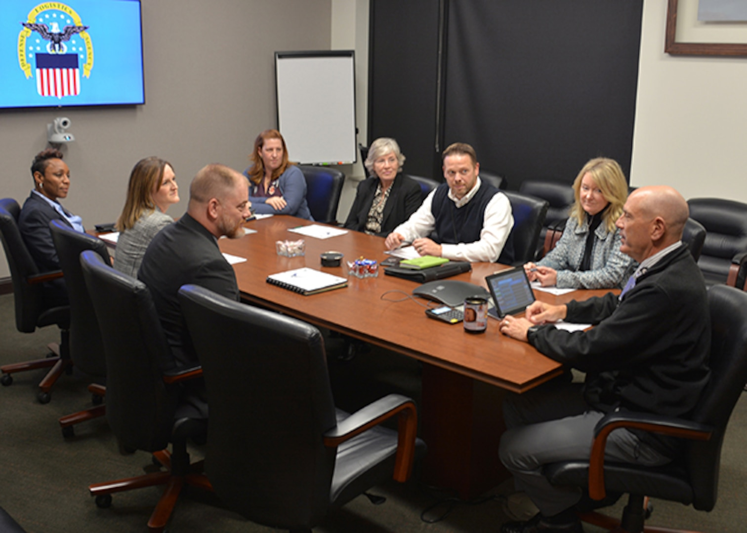 Air Force and Aviation employees talk around conference table