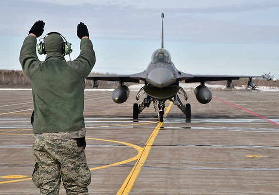 A crew chief guides F-16 aircraft to a stop.