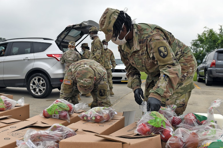 Members of the Louisiana National Guard, 205th Engineer Battalion, help distribute food for the Great Baton Rouge Food Bank in Walker, Louisiana, April 9, 2020. Guard members have helped package and distribute over 580,540 pounds of food while assisting five food banks throughout the state.
