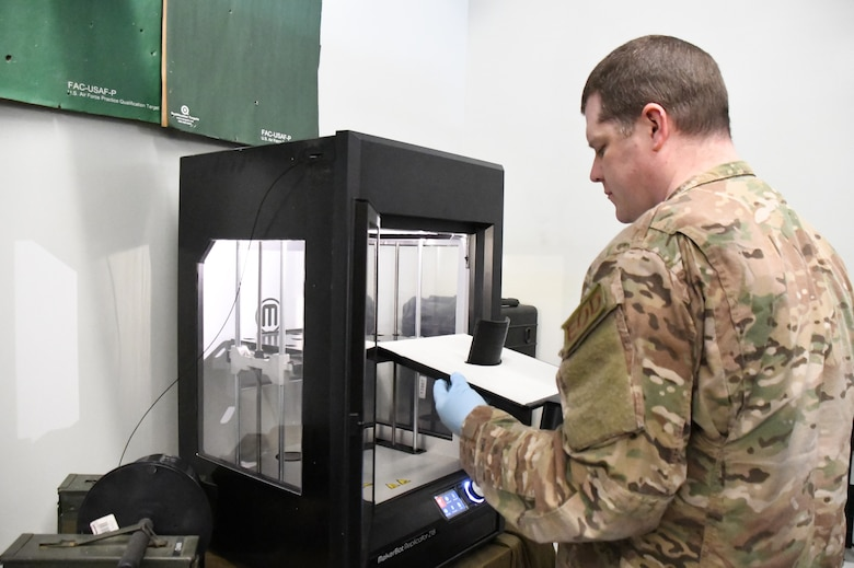 Senior Master Sgt. Jeremiah Mcclosky, Explosive Ordnance Disposal Superintendent, 104th Fighter Wing, prints a protective mask from a 3D printer for the 104th Fighter Wing Medical Group. The 104th Fighter Wing Medical Group is responding to state COVID-19 response efforts throughout the state of Massachusetts. (U.S. Air National Guard photo by Airman 1st Class Sara Kolinski)