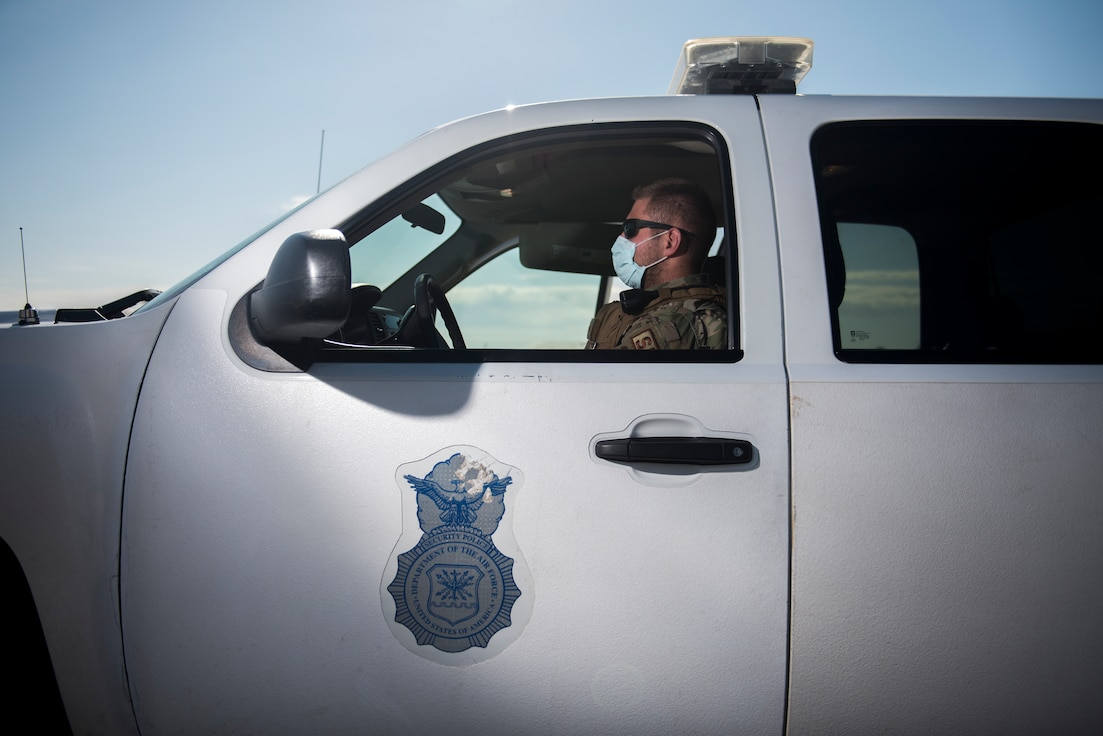 A security forces patrolman sits in his truck while wearing a cloth mask.