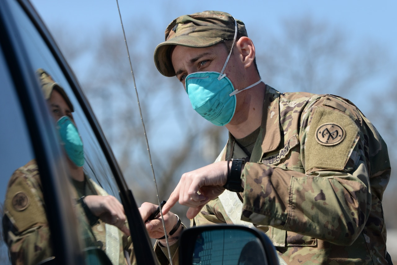 A soldier wearing a blue face mask checks a motorist's identification.