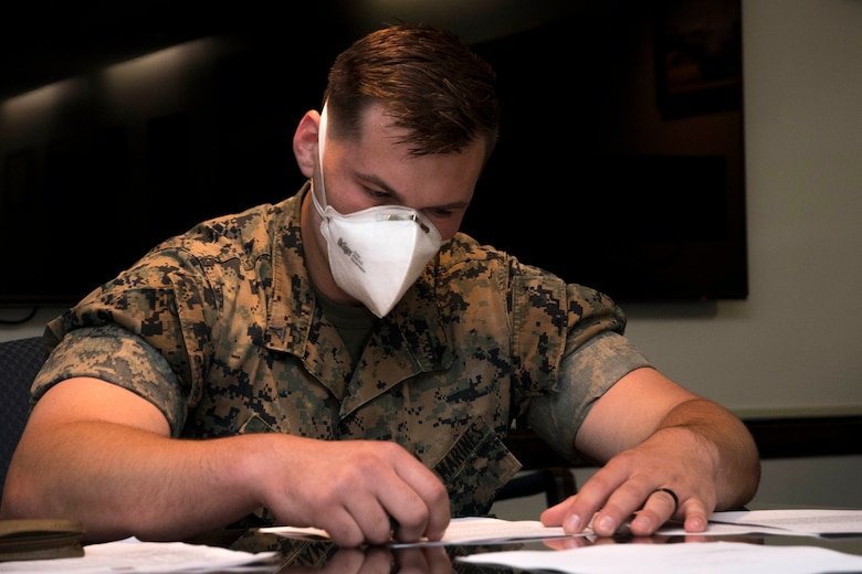 A Marine wears a face mask while completing a legal form worksheet in the wing conference room at Dobbins Air Reserve Base on April 9, 2020. This week, the Dobbins legal office helped more than 60 Marines with legal documents in preparation for a short-notice deployment to assist in the battle against COVID-19. (U.S. Air Force photo/Andrew Park)