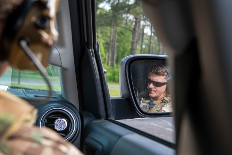 TACP officer talks on a radio in a car