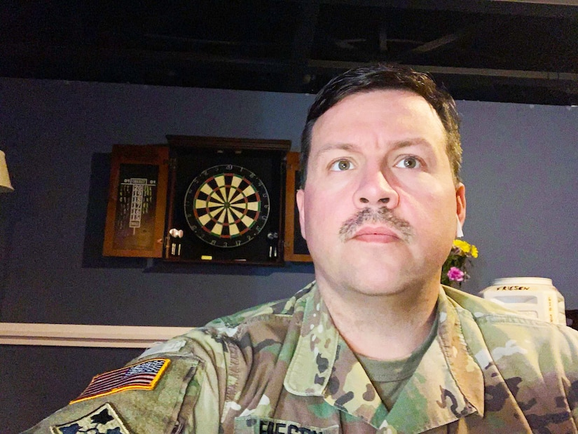 white male with mustache in green camouflage uniform with dark gray wall and dart board behind him.