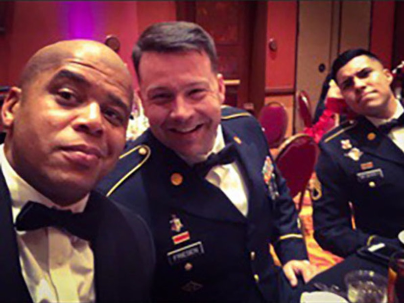 One black male in black suit with bow tie, one white male in dark blue dress uniform and bow time, and one Hispanic male in dark blue dress uniform with bow tie seated at a table.