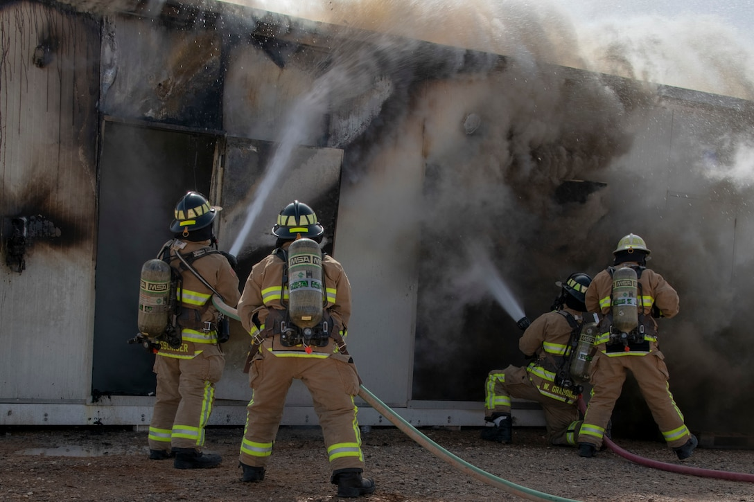 Four firefighters spray a fire with hoses.