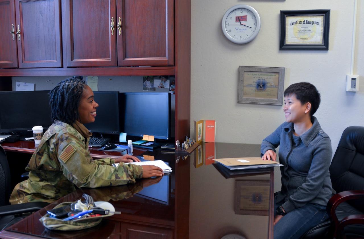 Two women sit across a desk chatting.