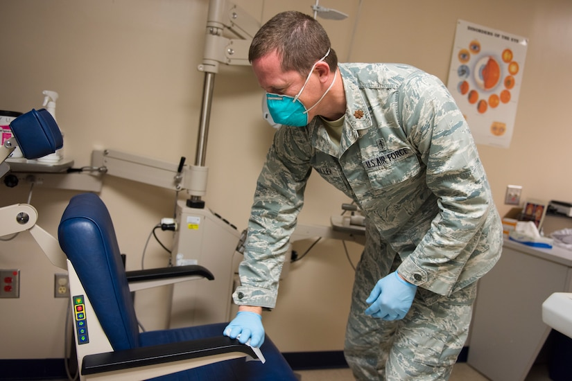 Major Bryan Sixkiller, an optometrist assigned to the 628th Medical Group, Operational Medical Readiness Squadron, cleans equipment at the Optometry Clinic at Joint Base Charleston, S.C., April 7, 2020. Optometry is taking safety measures such as limiting face-to-face time, wearing masks and gloves, frequently washing hands and cleaning medical equipment before and after each examination.