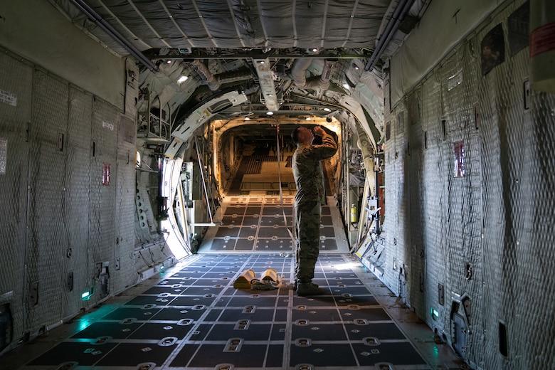 Flight engineer conducts pre-flight checks on a C-130
