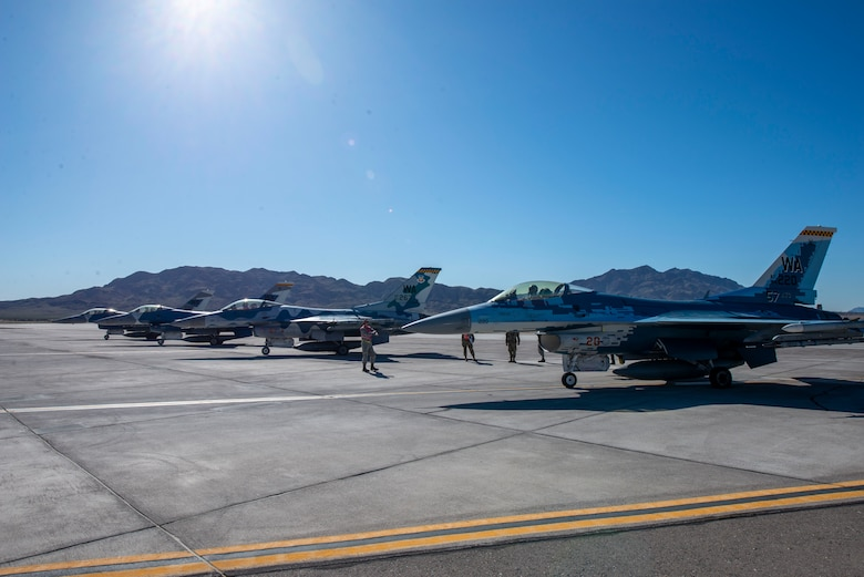 Four F-16 Fighting Falcon fighter jets sit at the end of the runway.