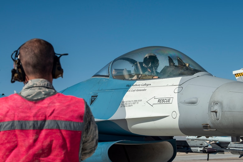 An F-16 Fighting Falcon fighter jet pilot waits for an Airman to signal them.