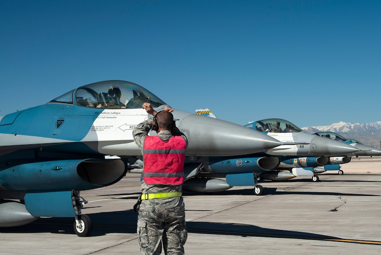 An Airman signals and F-16 Fighting Falcon fighter jet pilot.