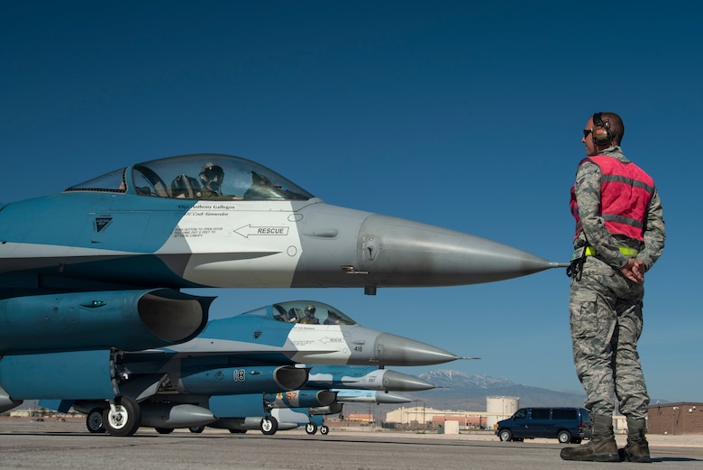 An Airman stands on front of a row of F-16 Fighting Falcon fighter jets.