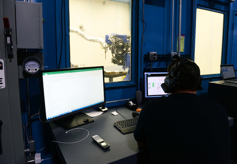 The additive manufacturing facility site manager inputs controls into a cold spray machine.