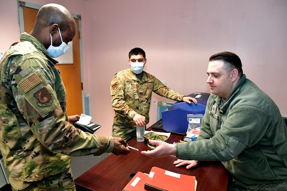 Tech. Sgt. Yves'denis Etiki handing his ID to another Airman during his out processing appointment.