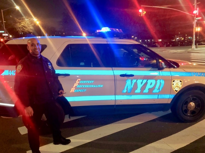 Master Sgt. Andy A. Jean-Pierre with his NYPD patrol vehicle.