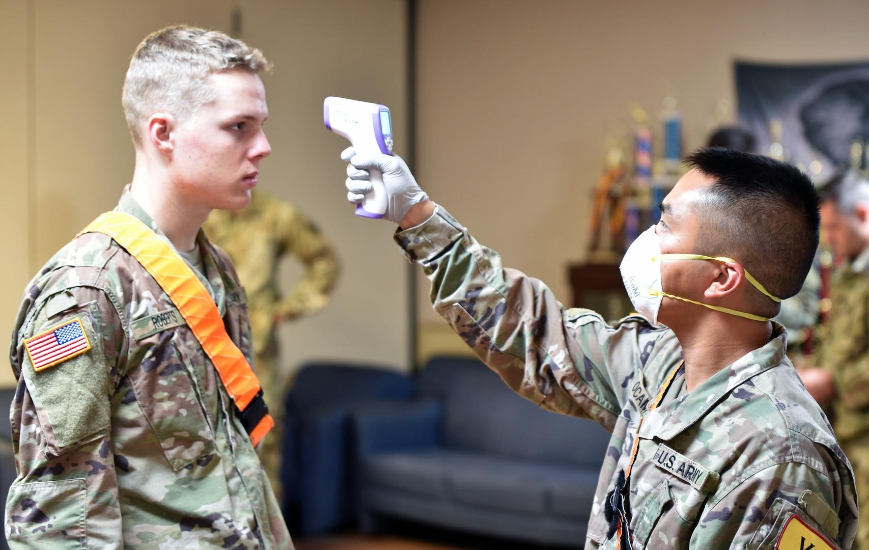 Soldier takes temperature.