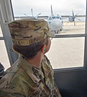 Soldier looks through bus window.