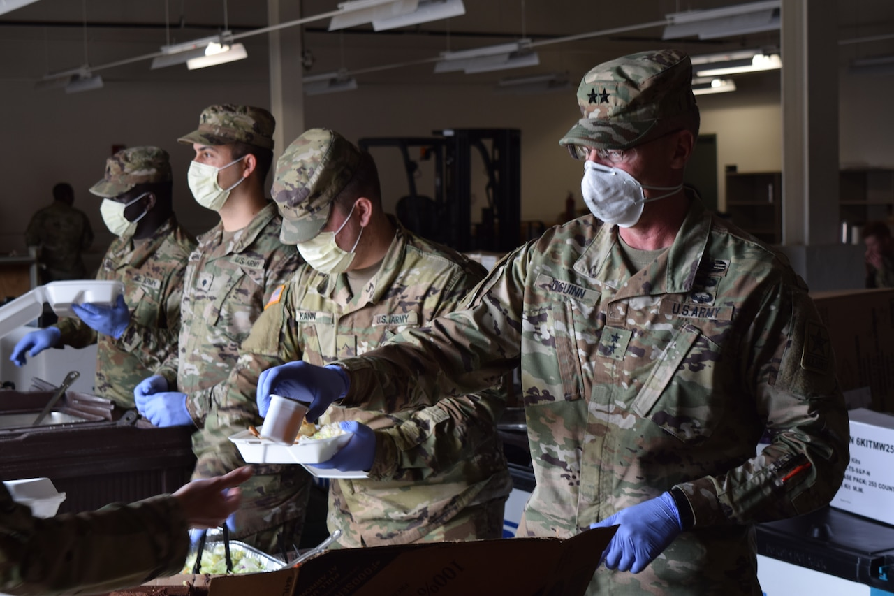 Soldiers wearing medical masks and gloves serve food.